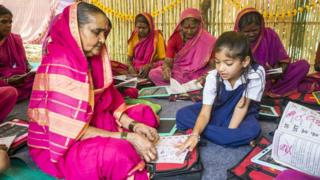Ramabhai Ganpat learning from little girl in school uniform