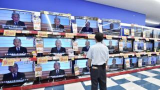 A man looks at television screens showing a speech by Japanese Emperor Akihito to the nation, are displayed at an electronic shop in Tokyo on August 8, 2016.