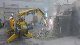 Robotic machine demolishing parts of the interior of a building at Dounreay