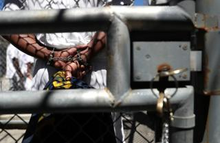 An inmate stands with handcuffs at San Quentin State Prison in California.