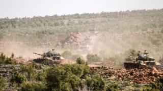 Turkish troops advance near Syrian border throw bush landscape