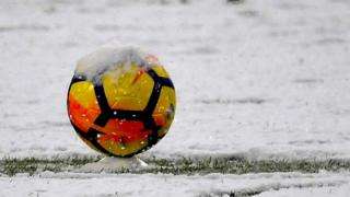 Yellow and orange football on a snowy pitch