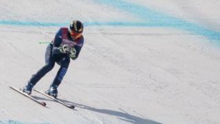 Chris Lloyd skiing down slope on snow