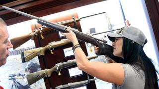 Una mujer prueba un rifle