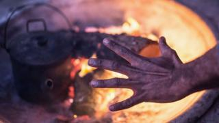 A resident of the Aboriginal tent embassy warms his hands on a fire in Redfern, Sydney, in 2015