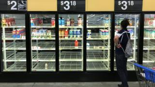Woman looks over bare refrigerator shelves in a Walmart in Houston