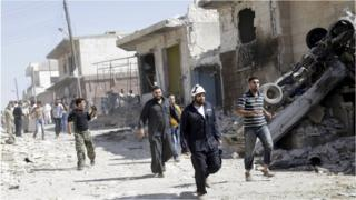 Civil defence members and civilians search for survivors at a site of an apparent government airstrike in the Syrian village of Talmenes