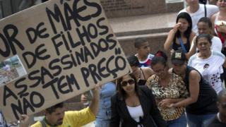 """Man holds sign that reads """"The sadness of mothers of children killed, doesn't have a price"""" at funeral for Eduardo Victor. 30 Sept 2015"""
