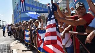 Cubans hold US as well as Cuban flags outside the US embassy building as the US flag is actually raised over the item in Havana on August 14, 2015, during US Secretary of State John Kerry's visit