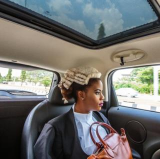 A Nigerian law graduate looks out of a car window
