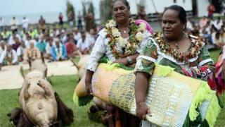 Women in traditional costumes bring presents to French President Francois Hollande during a ceremony in Wallis island, on February 22, 2016