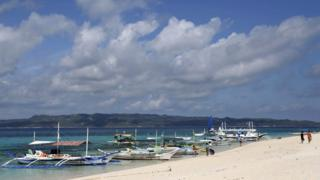 Traditional boats line up the shore in a secluded beach on the island of Boracay