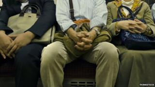 Homem sentado entre dois outros no trem