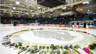 Flowers lie on the ice as people gather for a vigil at the Elgar Petersen Arena, home of the Humboldt Broncos