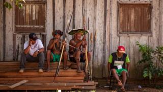 Members of the Cinta Larga sit by the side of a house with bows and arrows