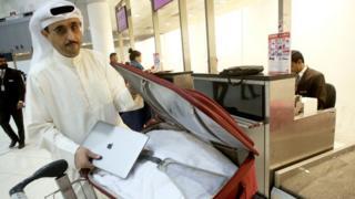 Mwanaharakati wa Kuwait Thamer Bourashed akiweka laptopu yake ndani ya mzigo kabla ya kuabiri ndege