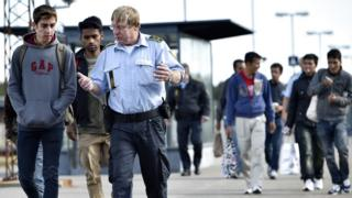 Refugees speak with a Danish policeman after arriving in Rodby, southern Denmark 7 September 2015.