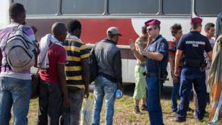 A Hungarian police officer controls a queue of migrants in Szeged, 31 Aug 15