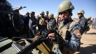 Un policía iraquí inspecciona sus armas en la base militar Qayyarah cerca de Mosul