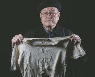 潘信行依舊保存著父親受刑時所穿、被彈孔穿過的衣服。