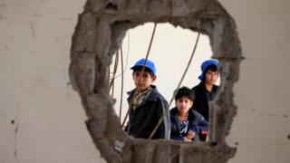 Boys look through a hole in a wall in their school in Sanaa, Yemen, reportedly caused by a Saudi-led coalition air strike (5 October 2016)