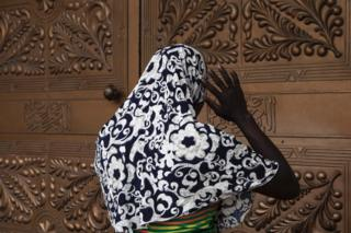 A Muslim woman is praying at the entrance of the Central Mosque in Lagos on July 5, 2016 during public holidays marking the end of the Muslim holy month of Ramadan
