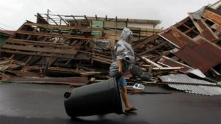 Mulher caminha em frente a uma construção derrubada pelo furacão Maria em Fajardo.