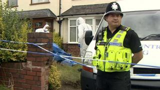 Police officer and forensics team outside a house