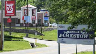 """Welcome to Jamestown"" sign by the road, and main chains in the background: Walgreens and KFC"