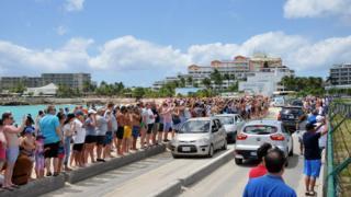 Image of people watching planes take off in Sint Maarten, taken at Maho Beach