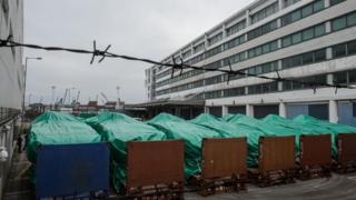 Armoured vehicles belonging to the Singapore military are seen covered with tarpaulin at a customs facility in Hong Kong