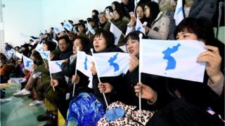 "People wave the Korean Unification Flag, while the joint Korean women""s hockey team faces Sweden - 5 February 2018"