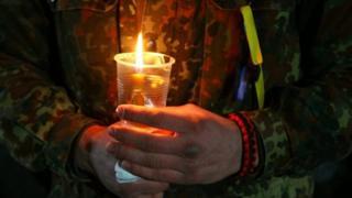військовий тримає свічку
