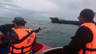 Armed Philippine Coast Guard personnel escort Vietnamese vessel MV Giang Hai, which was attacked by pirates, to Taganak anchorage area in Tawi-Tawi, southern Philippines, on 21 February 2017.