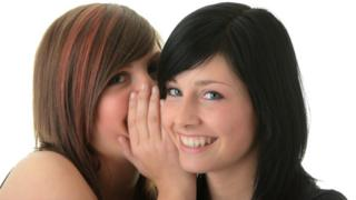 Young women whispering