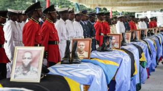 "Soldiers of Tanzania People""s Defence Force (TPDF) stand beside the coffins of Tanzanian peacekeepers who were killed by by suspected Ugandan rebels, at the headquarters of Tanzania People""s Defence Force in Dar es Salaam on December 14, 2017."