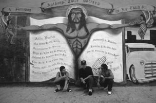 Three men sit in front of a mural depicting Jesus