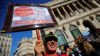 A demonstrator holds a placard with a picture of French President Emmanuel Macron as he attends a national strike and protest against the governments labour reforms in Marseille