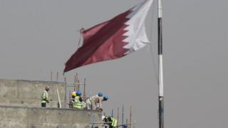 Construction workers are pictured on a building site on May 9, 2014 in Doha, Qatar