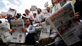People reading newspapers in protest