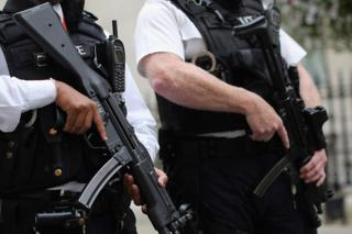 Armed police officers stand in Downing Street
