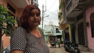 Sunita Devi in front of her house