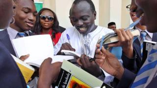 Nigerian poet Tade Ipadeola signs books after he was awarded with the prestigious Nigeria Prize for Literature during a ceremony in Lagos on 6 March 2014
