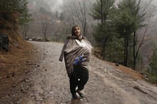 A Kashmiri woman carries a newborn baby inside her 'phiran', a traditional Kashmiri dress, as she escapes artillery fire.
