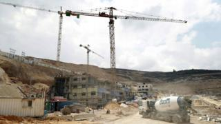 Photo taken on 14 April 2016 shows workers at a construction site in the Jewish settlement of Givat Zeev in the occupied West Bank
