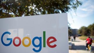 A man rides a bike passed a Google sign and logo at the Googleplex in Menlo Park, California on November 4, 2016.