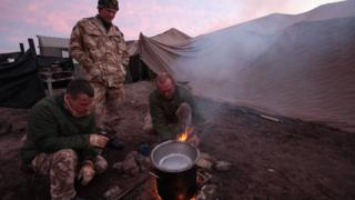 Soldiers cooking rations over a stove
