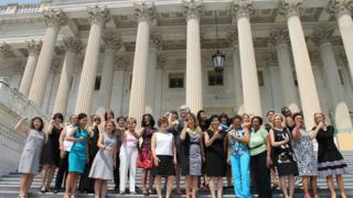 Women gather on the steps of Congress on Friday wearing outfits with no sleeves