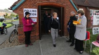 A voter leaves Trumpington village hall in Cambridgeshire