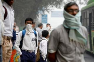 A schoolboy covers his face with a handkerchief as he waits for a passenger bus on a smoggy morning in New Delhi, India, November 8, 2017